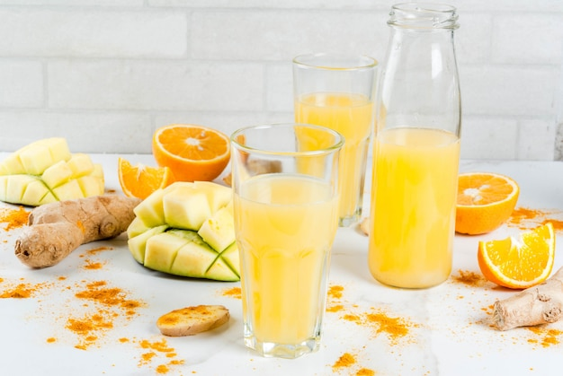 Traditionele smoothie van mango, sinaasappel, kurkuma en gember Premium Foto