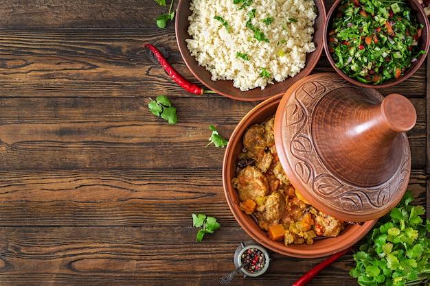 Traditionele tajine gerechten, couscous en verse salade op rustieke houten tafel. tajine lamsvlees en pompoen. bovenaanzicht plat leggen Premium Foto