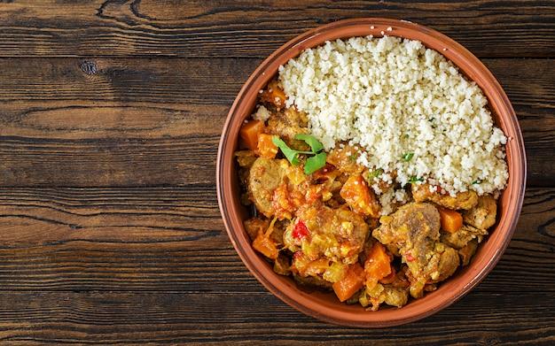 Traditionele tajine gerechten, couscous en verse salade op rustieke houten tafel. tajine lamsvlees en pompoen. bovenaanzicht plat leggen Gratis Foto