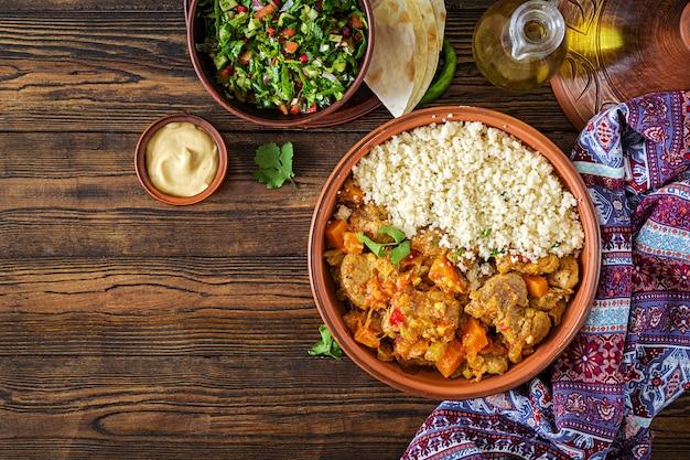 Traditionele tajine gerechten, couscous en verse salade op rustieke houten tafel. Premium Foto
