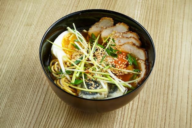 Traditionele thaise ramen soep met noedels, vlees, shiitake champignons en ei in een zwarte kom op een houten oppervlak Premium Foto