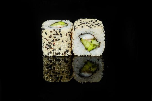 Traditionele verse japanse sushibroodjes op een zwarte achtergrond Premium Foto