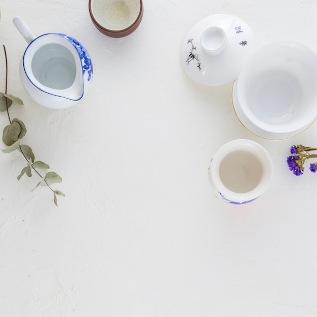 Traditionele witte en blauwe koffiekop en theepot op witte achtergrond Gratis Foto