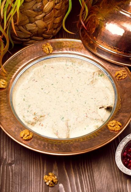 Traditionele yayla-soep (yoghurtsoep) in koperen plaat met walnoten Gratis Foto