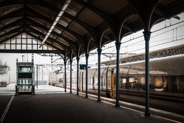 Train in een treinstation dat in de winter met sneeuw bedekt is Gratis Foto