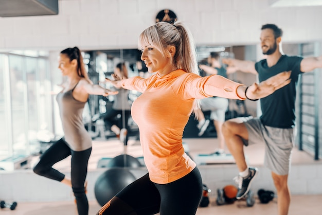 Trainer die aan de groepssaldooefening toont in gymnastiek. op de achtergrond hun spiegelreflectie. selectieve aandacht op blonde vrouw. Premium Foto