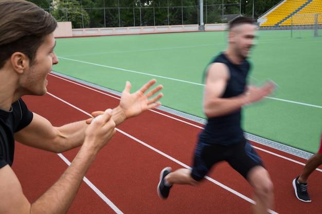 Trainer die dichtbij jonge multi-etnische atletenmannen gilt Gratis Foto