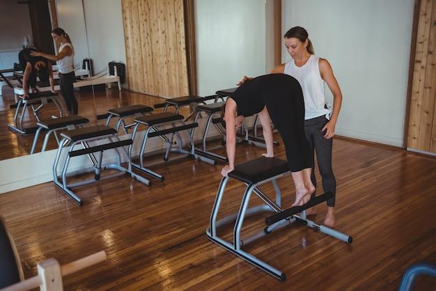 Trainer die een vrouw helpt tijdens het beoefenen van pilates Gratis Foto