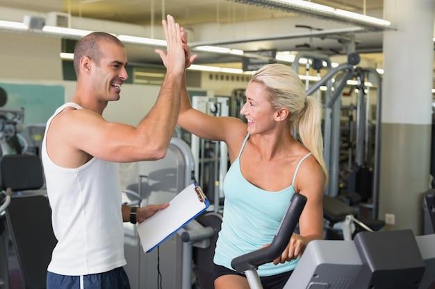 Trainer die hoge vijf geeft aan zijn cliënt op hometrainer bij gymnastiek Premium Foto