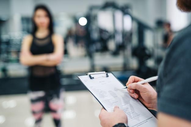 Trainer en cliënt bespreken haar vorderingen in de sportschool. gym instructeur schrijven op klembord Premium Foto
