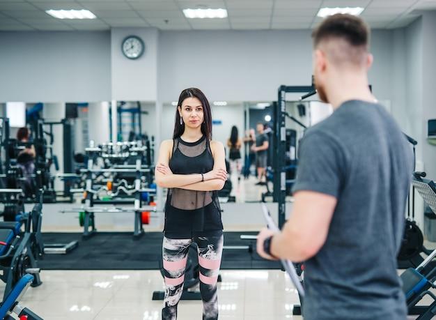 Trainer en cliënt bespreken haar vorderingen tijdens de oefening in de sportschool. persoonlijke fitnessinstructeur. Premium Foto