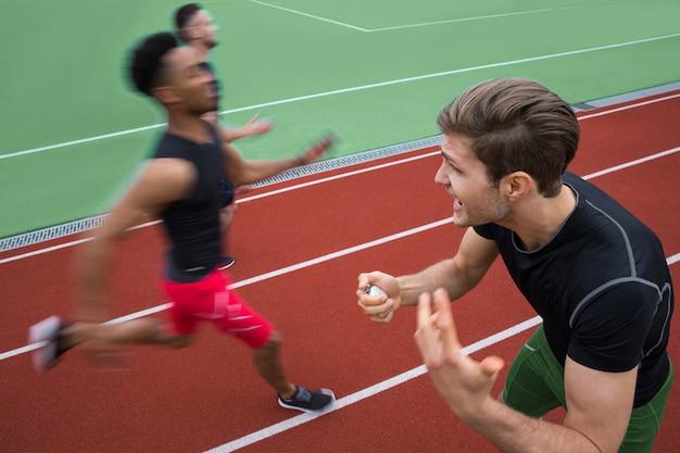 Trainer schreeuwen in de buurt van jonge multi-etnische atletenmannen lopen Gratis Foto