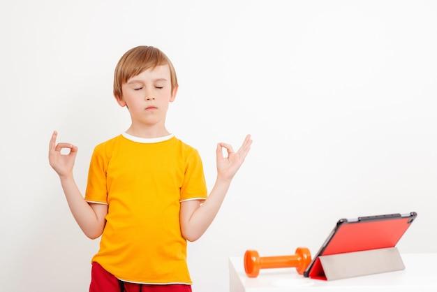 Training op afstand. jongen doet yoga oefening thuis. kinderen sporten. online training. Premium Foto