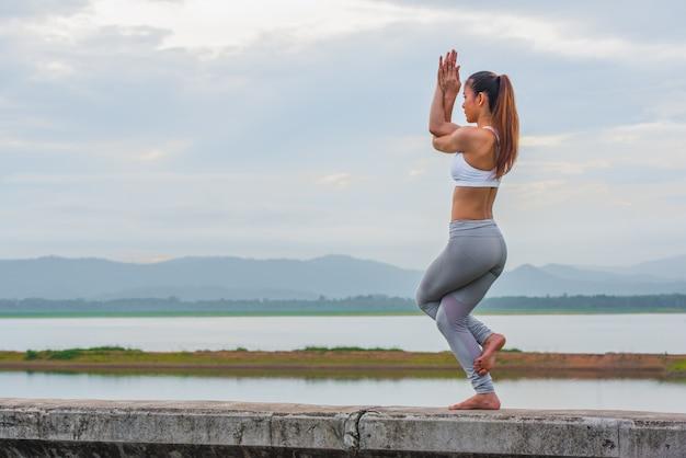 Training yoga, jonge vrouw doet yoga oefening op de muur in prachtige bergmeren Premium Foto