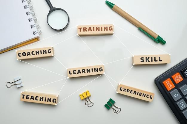 Trainingsconcept - houten blokken met inscripties coaching, leren, vaardigheid, lesgeven. Premium Foto
