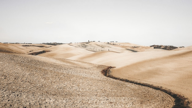 Traject in een woestijn die leidt naar de stad onder de heldere hemel Gratis Foto