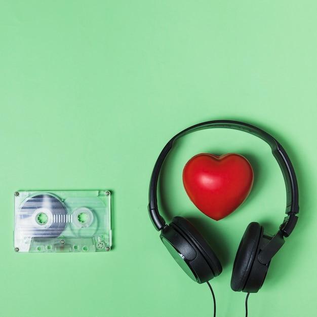 Transparant cassettebandje; hoofdtelefoon en rood hart op groene achtergrond Gratis Foto
