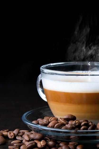 Transparant glazen kopje cappuccino met zichtbare lagen koffie, melk en schuim en bonen op zwart Premium Foto