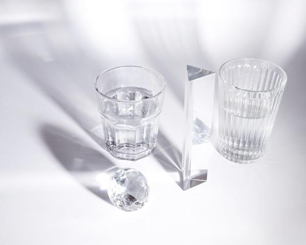 Transparante glazen water; diamant en prisma op witte achtergrond met schaduw Gratis Foto