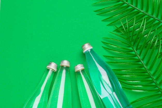 Transparante vloeibare fles met tropische palmbladen, bovenaanzicht Premium Foto