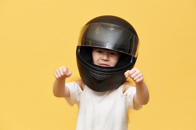 Transport, extreme, motorsport en activiteitenconcept. portret van gevaarlijke kleine meisje ruiter in zwarte beschermende motorhelm handen voor haar houden alsof het rijden motor Gratis Foto