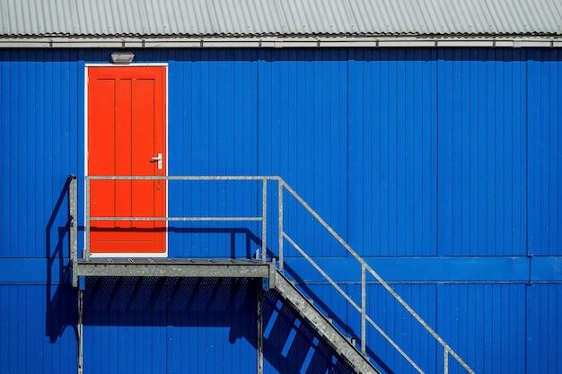Trap bij de blauwe muur van een garage die naar de rode deur leidt Gratis Foto