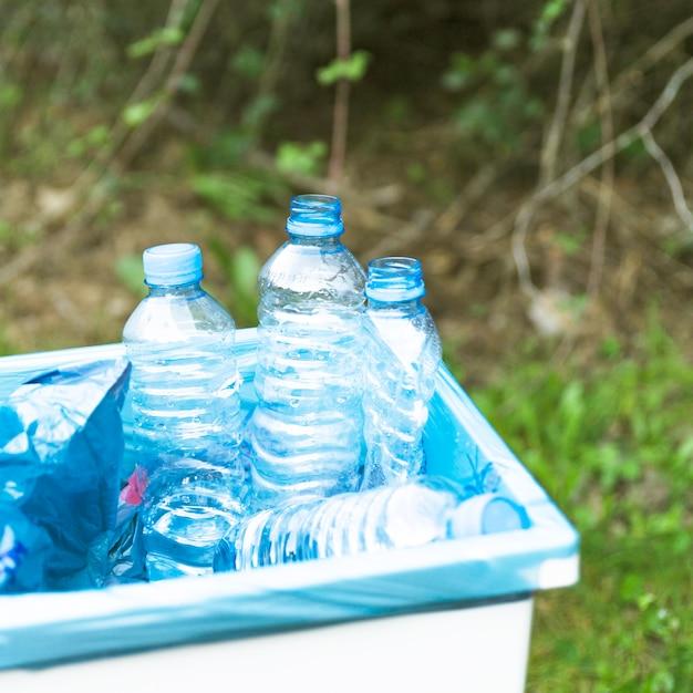 Trashcan met plastic huisvuil in openlucht Gratis Foto