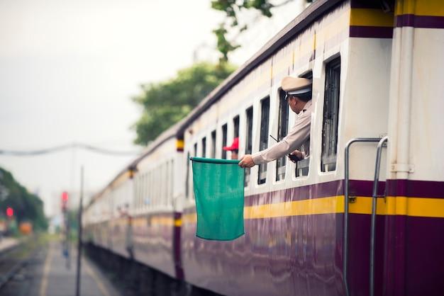 Treinfunctionarissen signaleren groene vlaggen voor treinen om mensen van het treinstation naar de hoofdstad te vervoeren Premium Foto