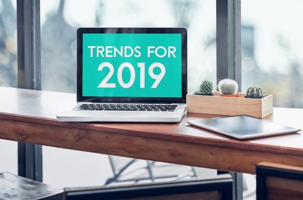 Trends voor 2019-woord in laptop het computerscherm met tablet op hout bevonden lijst Premium Foto