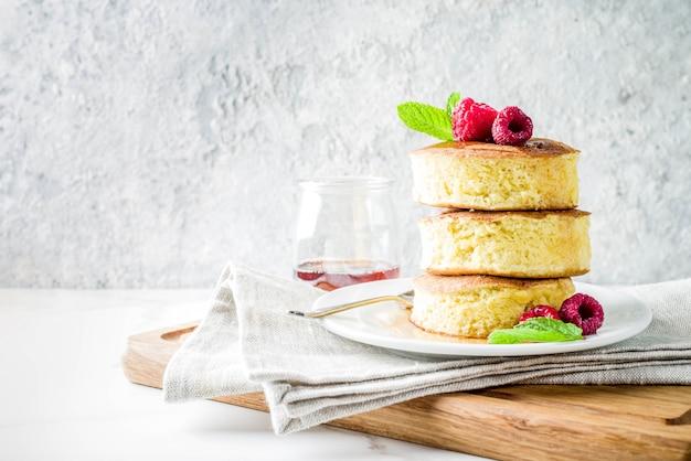 Trendy aziatisch eten, pluizige japanse soufflépannenkoeken, hotcakes met ahornsiroop en frambozen lichte betonnen tafel Premium Foto