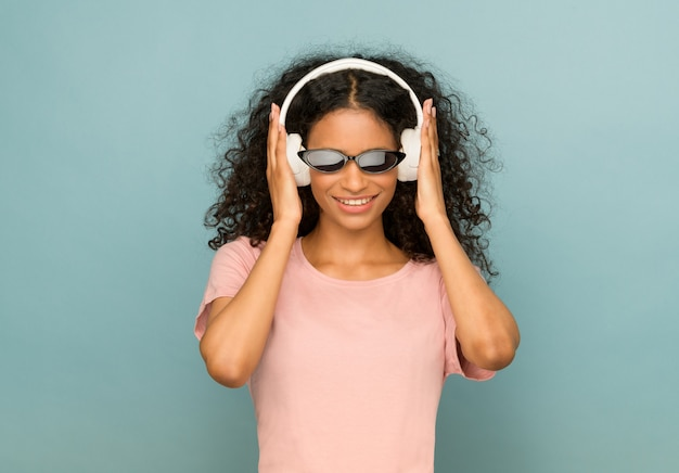 Trendy jong afrikaans amerikaans meisje dat zonnebril en hoofdtelefoons draagt Premium Foto