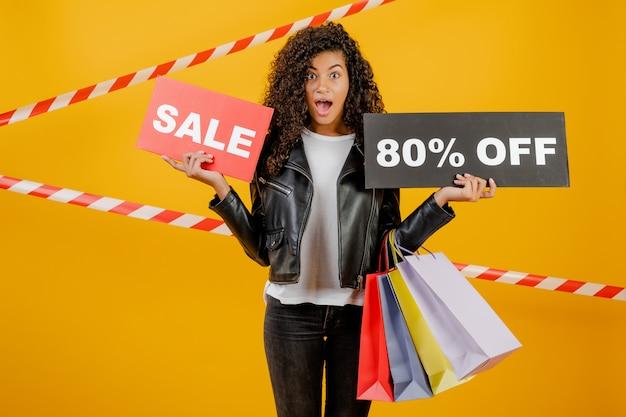 Trendy jong zwart meisje met verkoop 80% teken en kleurrijke boodschappentassen geïsoleerd over geel met signaalband Premium Foto