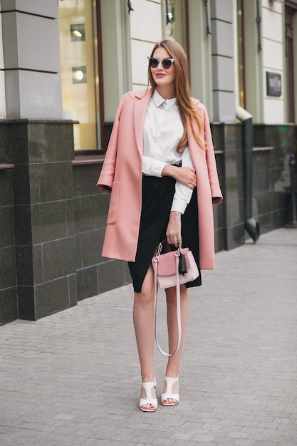 Trendy jonge stijlvolle mooie vrouw die in de straat loopt, roze jas draagt, tas, zonnebril, wit overhemd, zwarte rok, mode-outfit, herfsttrend, glimlachend gelukkig, accessoires Gratis Foto