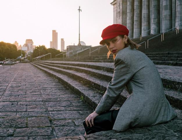 Trendy jonge vrouw zitten in de buurt van de trap kijken over de schouder Gratis Foto