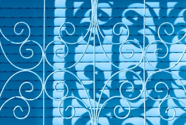 Trendy kleur van het jaar 2020. close-up van metalen beschermingsrooster. gebogen staal. textuurrooster met ornament Premium Foto
