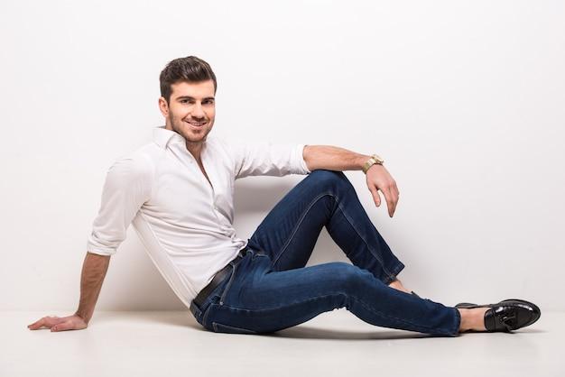 Trendy man zit op de vloer Premium Foto