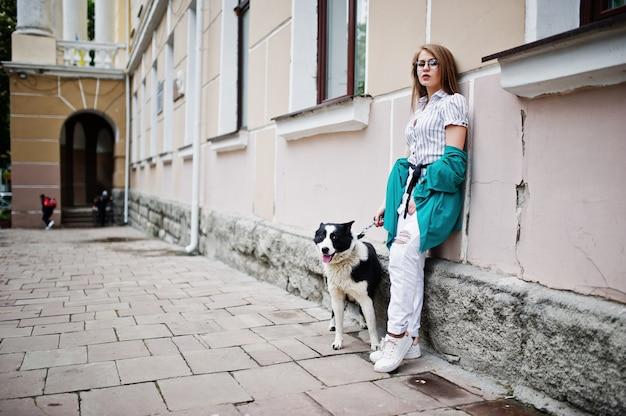 Trendy meisje op bril en gescheurde spijkerbroek met russisch-europese laika (husky) hond aan de leiband, tegen straat van de stad Premium Foto