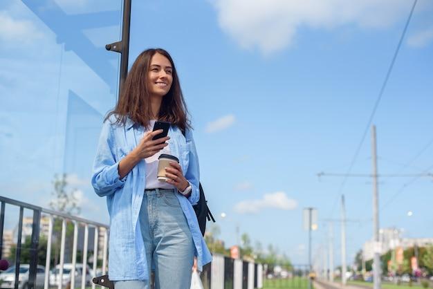 Trendy meisje wacht 's ochtends op bus of tram op ov-station. jonge vrouw met een kopje koffie en smartphone monitoring transport via de app. Premium Foto