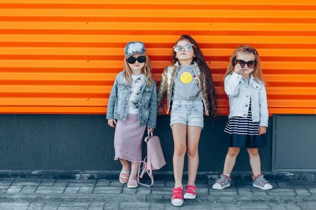 Trendy meisjesteam in zonnebril die op een zonnige dag stellen Premium Foto
