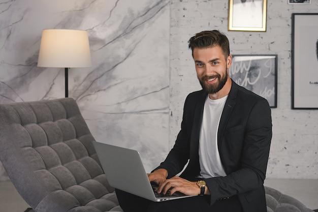 Trendy ogende positieve jonge ongeschoren mannelijke werknemer gekleed in stijlvolle luxe kleding met behulp van generieke laptopcomputer op sofa in moderne kantoren, vreugde over succes, breed glimlachend Gratis Foto