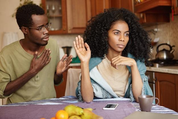 Triest afro-amerikaanse man in glazen met hand op de borst, excuses aan zijn boze en gekke vrouw Gratis Foto