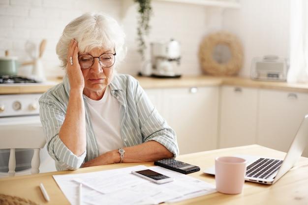Triest gefrustreerde senior vrouw gepensioneerde met depressieve blik, hand op haar gezicht houden, gezinsbudget berekenen, zittend aan het aanrecht met laptop, papieren, koffie, rekenmachine en mobiele telefoon Gratis Foto