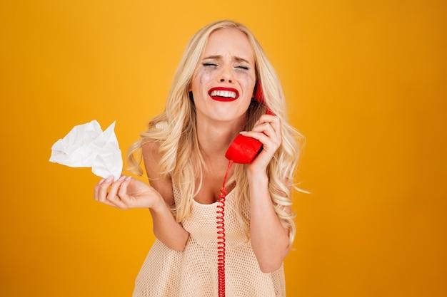 Triest huilende schreeuwende jonge blonde vrouw praten via de telefoon. Gratis Foto