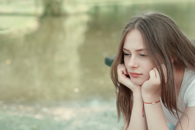 Triest jong meisje in de tienerleeftijd. sluit omhoog portret van vrouw het mediteren. buitenscène. kopieer ruimte. Premium Foto