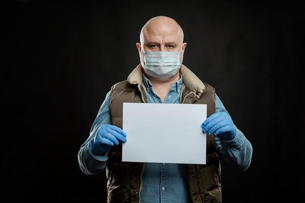 Triest kale man in een medisch masker en handschoenen met een leeg bord in zijn handen. ruimte voor tekst. werkloosheid en de wereldwijde crisis tijdens de pandemie van het coronavirus. Premium Foto