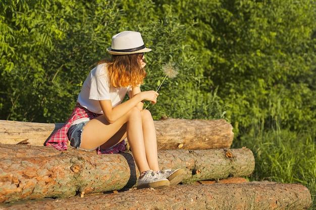 Triest meisje zit in de natuur met een pluizige paardebloem, ernstige ongelukkige tiener Premium Foto