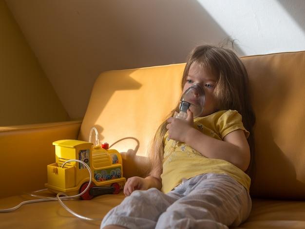 Triest ziek meisje in pyjama maakt inademing zittend op de bankkind is ziek Premium Foto