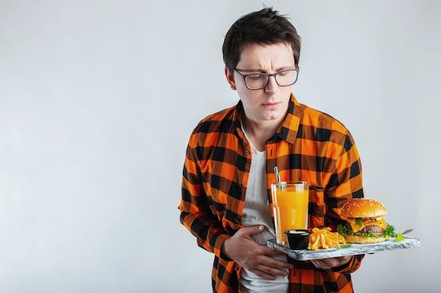 Trieste jonge man in shirt zet hand op pijn buik Premium Foto