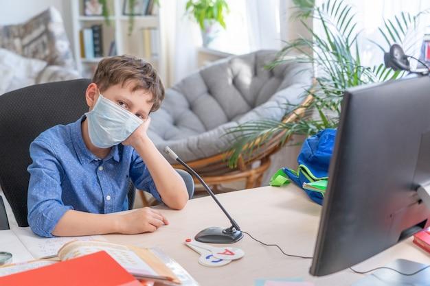 Trieste jongen in gezichtsmasker met behulp van computer huiswerk tijdens coronavirus quarantaine Premium Foto