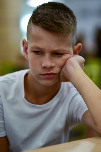 Trieste tienerjongen zittend op een stoel voor de tafel. Premium Foto